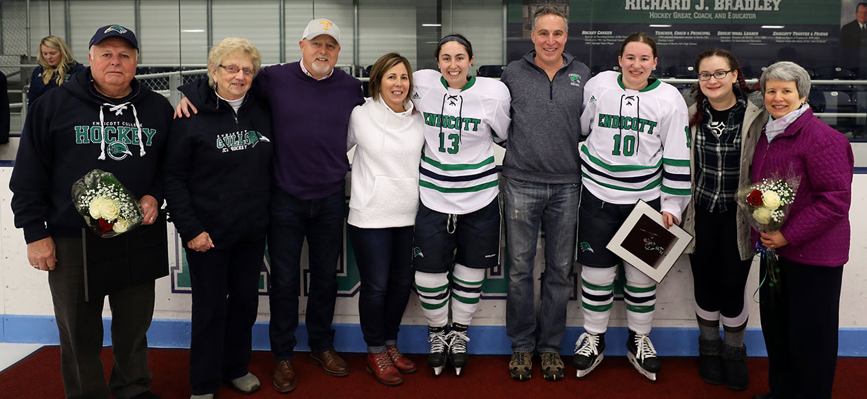 Endicott women's ice hockey seniors post for a photo with their families.