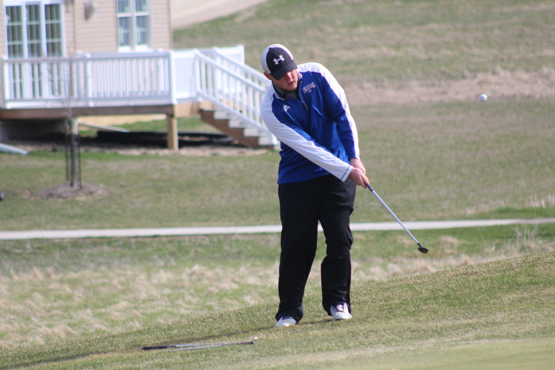 Zach Nicholson chips onto the green on Saturday at the Wartburg Invitational in Waverly.