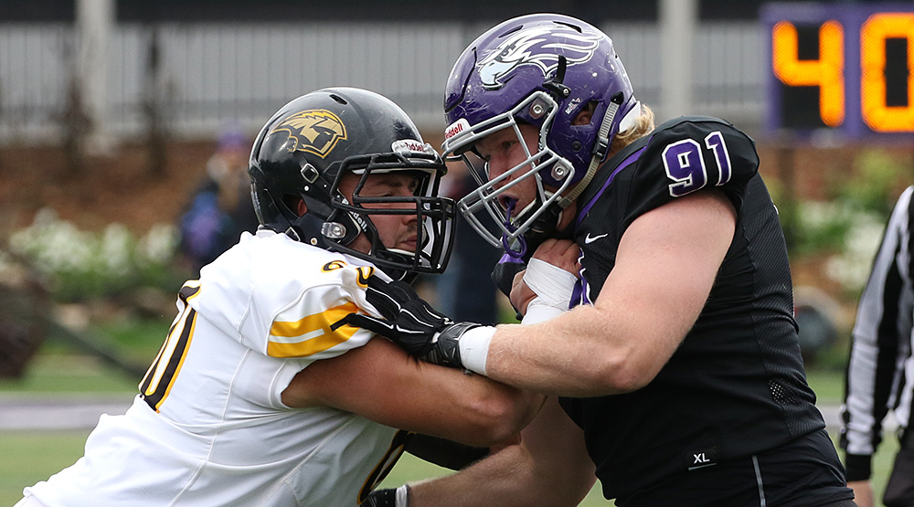 Oshkosh center Tyler Powers, in white jersey, squares off with UW-Whitewater defensive lineman Merritt Stott, in black jersey. (Photo by Daryl Tessmann, d3photography.com)