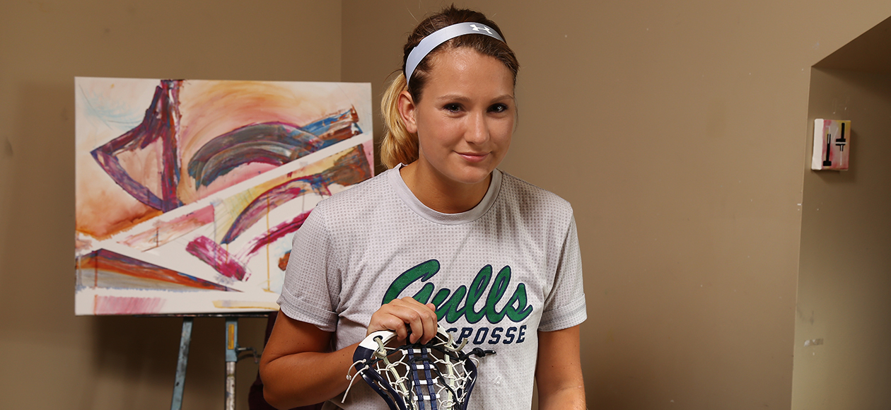 Senior women's lacrosse player Kendra Walkers poses with a smile in the art studio next to one of her paintings while holding her lacrosse stick.