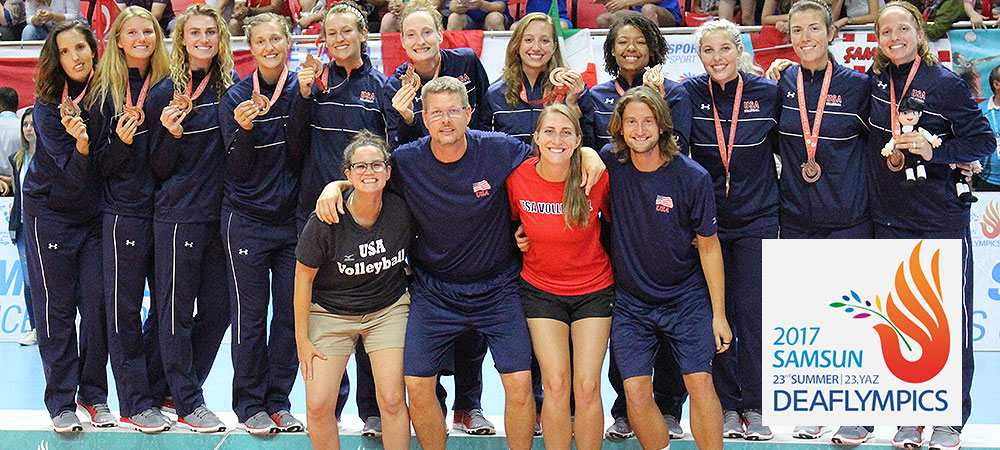 Team USA Deaf Women's Volleyball at the 2017 Deaflympics in Samsun, Turkey. The 11 players are standing on a podium with bronze medal medals around their necks. The players are in navy colored warm up suits. The 4 coaches are standing in front of the players with their arms around each other. Everyone is smiling and excited.