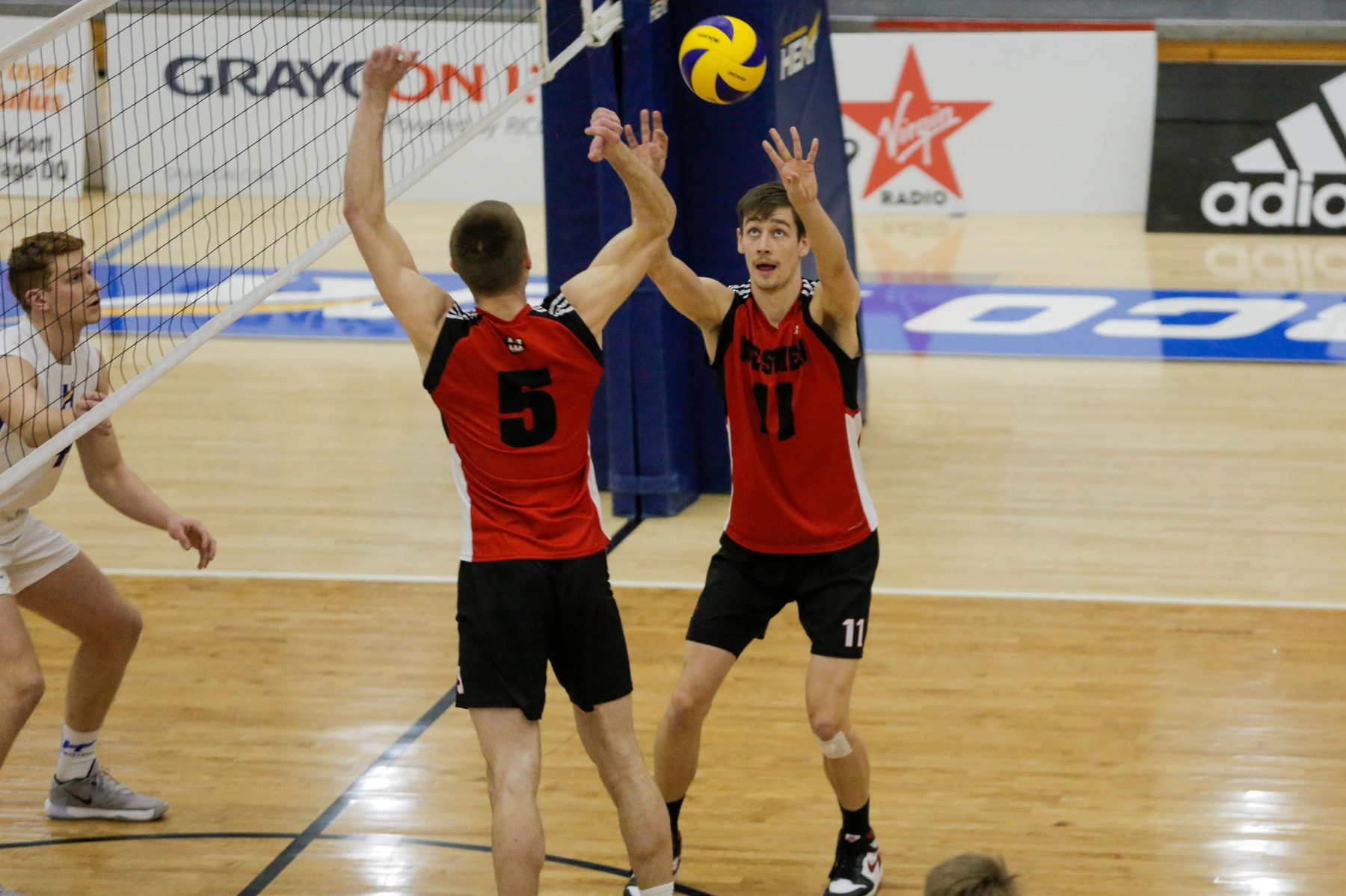 Mikael Clegg sets the ball while Keegan Teetaert (5) runs a middle attack during men's volleyball action against the UBCO Heat in Kelowna, B.C., on Saturday, Jan. 11, 2020. (UBCO Athletics photo)