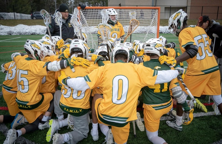 The men's lacrosse team huddles up in front of the goal for their pre-game prayer prior to a contest.