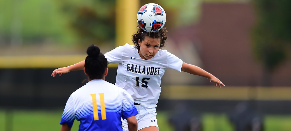 GU's Emelia Seldon heads a soccer ball over an opponent's head. She is wearing a white Gallaudet soccer uniform and the game is during the day time.