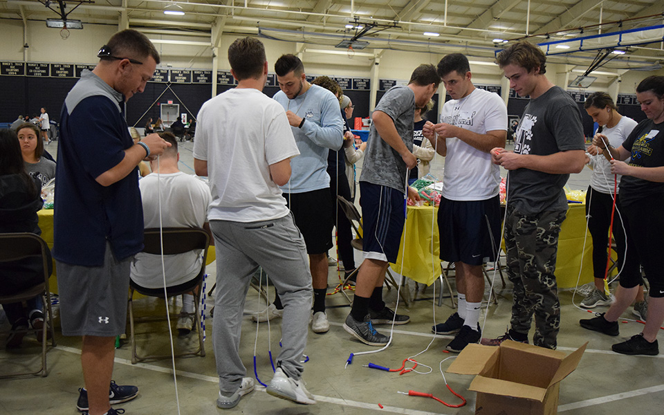 Members of Greyhounds' baseball and softball teams work on making jump ropes for the Boys & Girls Club as part of Moravian's Third Annual Heritage Day on September 26, 2018.