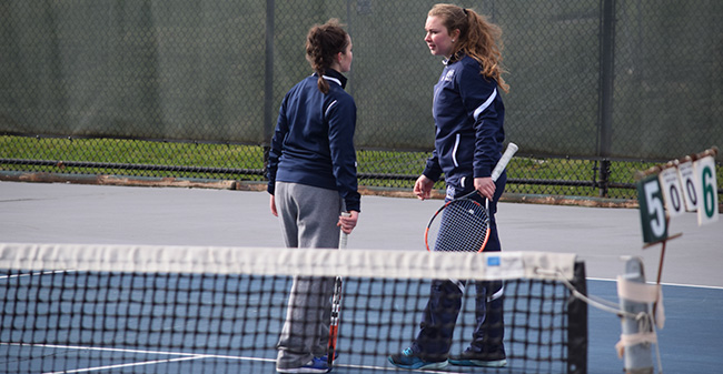 Lauren Steinert '20 and Mary Angle '21 talk during doubles action versus Ursinus College at Hoffman Courts.