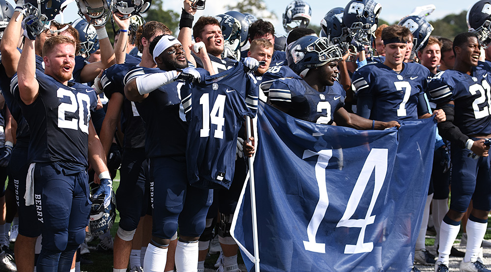 Justus Edwards' teammates hold up his uniform and a banner with Edwards' No. 14 on it. (Berry athletics photo)