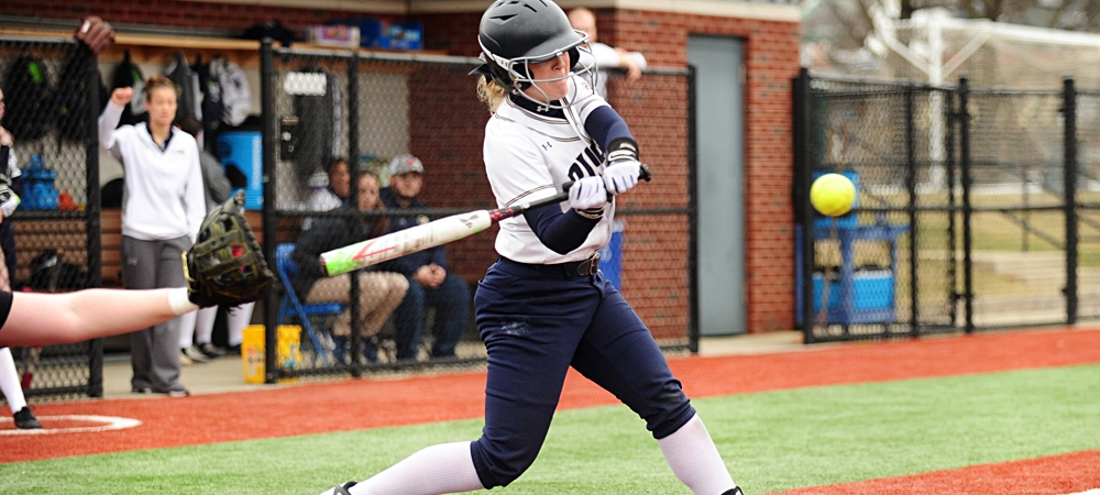 GU softball player Briana Pogue swings a bat towards a yellow softball during a Bison game.