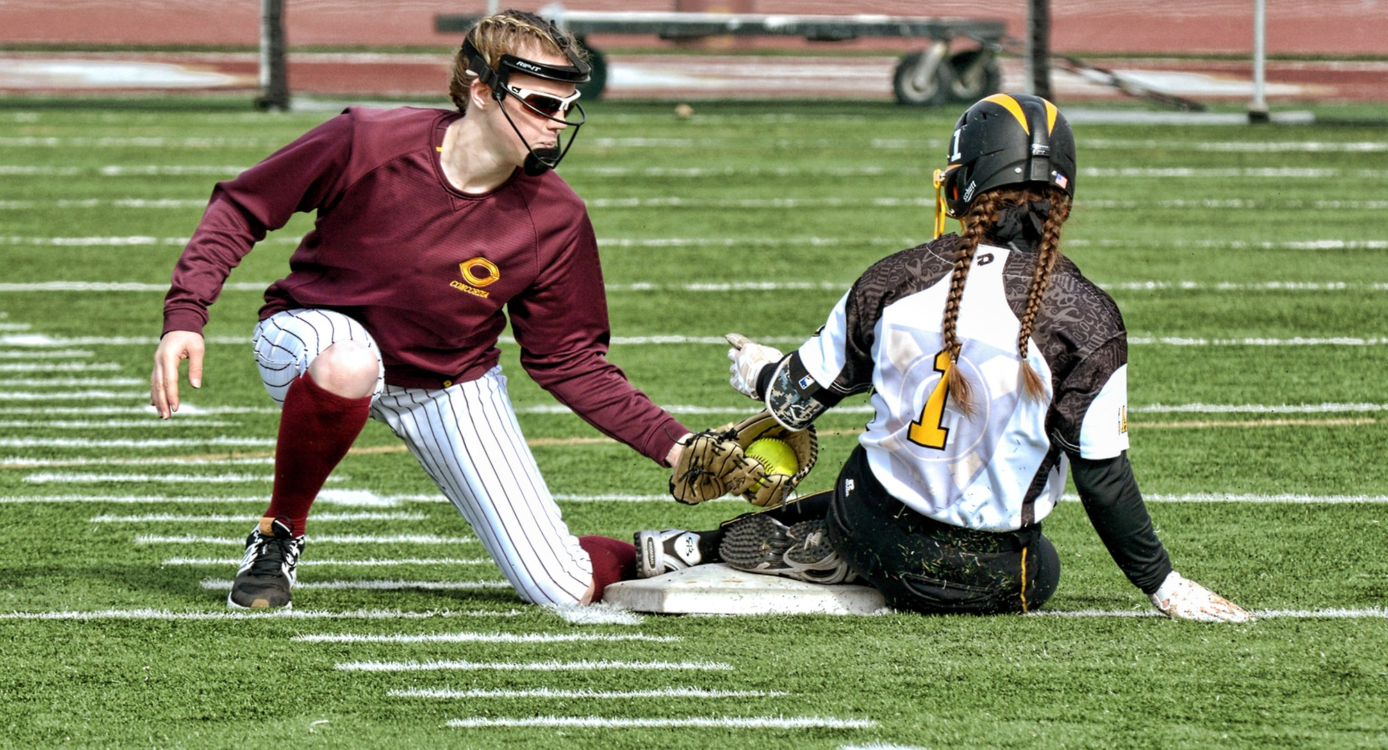 Cobber shortstop Megan Gavin puts the tag on a Gustavus base runner as she steals second base during the second game of the Cobbers' home opener with the Gusties.