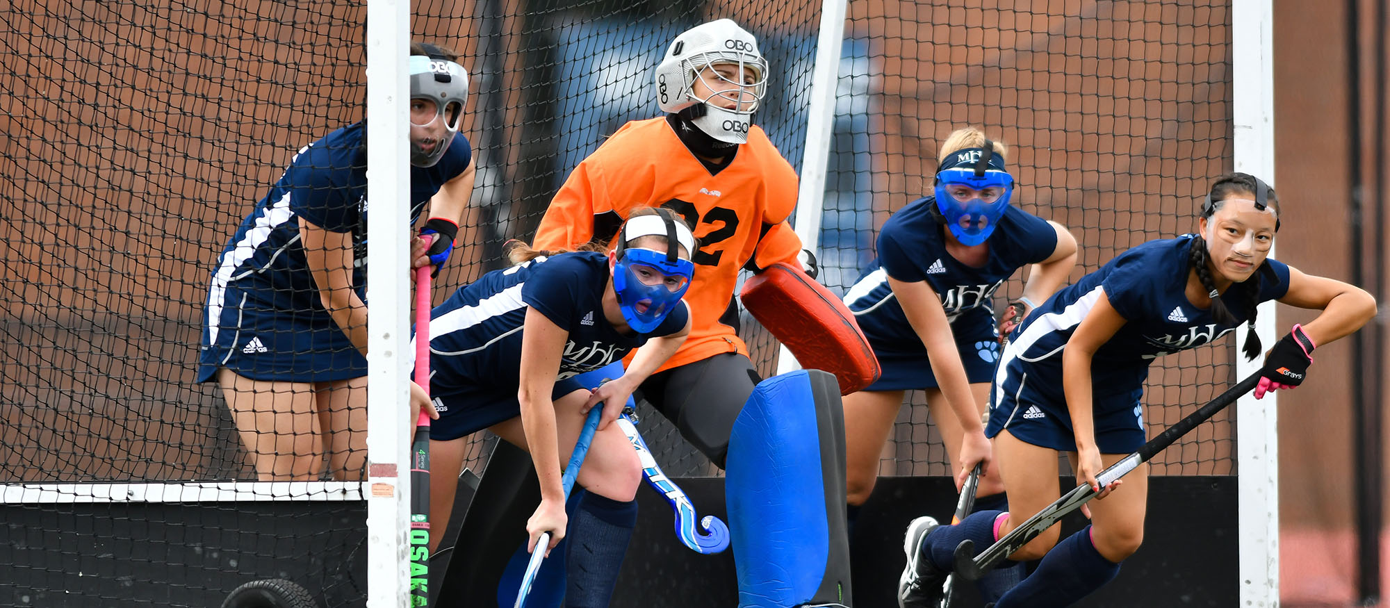 Action photo of the Lyons field hockey defense on a penalty corner.