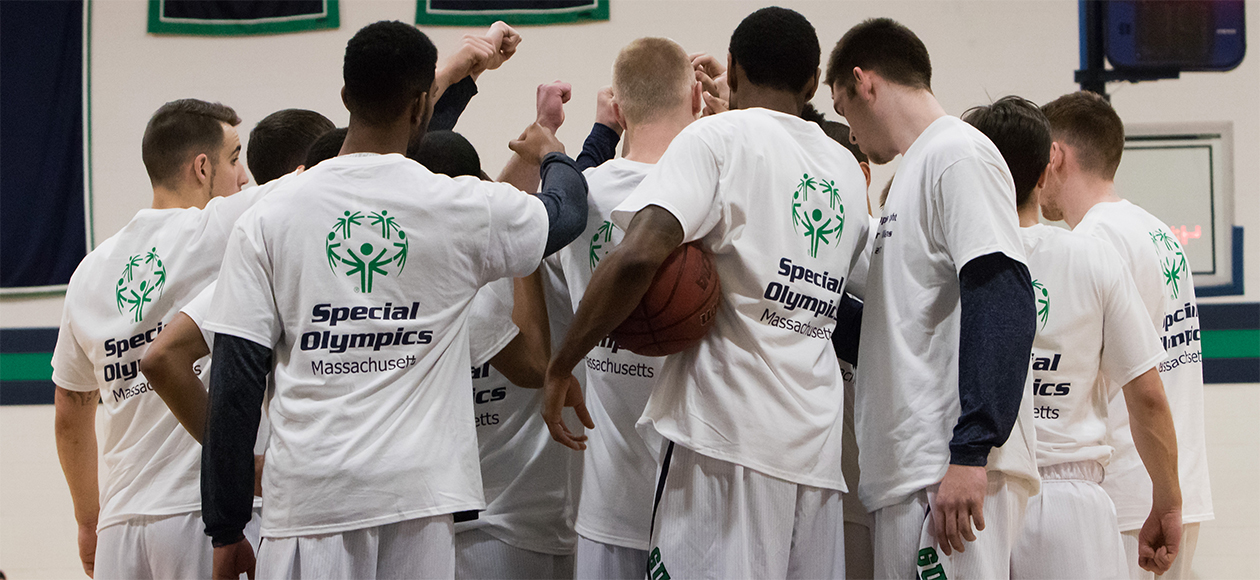The Endicott men's basketball team breaks a huddle wearing their white Special Olympics t-shirts.