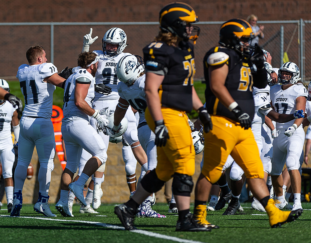 Scott Gustafson and teammates celebrate in the background, in focus, while Gustavus players walk off in the foreground