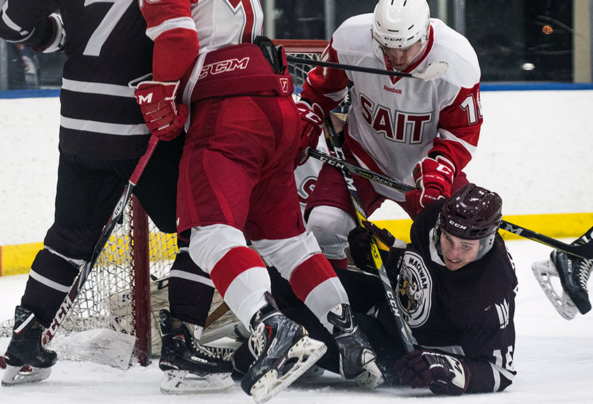 Ryan Baskerville gets some treatment from SAIT's Patrick Martens after getting in goalie Payton Lee's kitchen on Saturday night (Matthew Jacula photo).