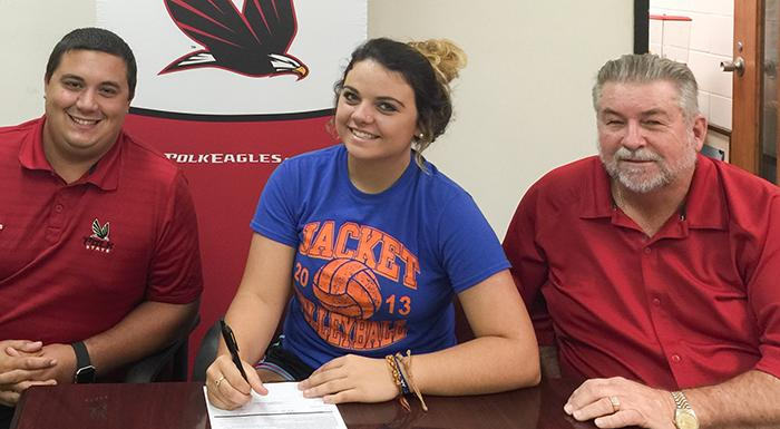 Alexis Sims signs letter of intent as Coordinator of Athletics Wally Minto (left) and Athletic Director Bing Tyus look on.