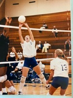 Mandy (Arnold) Rodriguez setting a ball for the Falcons