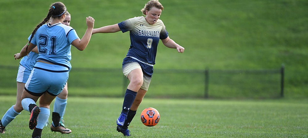 Gallaudet's Brittany Mallach dribbles the ball up the field. She is wearing a buff and blue soccer uniform. The soccer ball is orange and next to her right foot. Two defenders are off to the left of her.