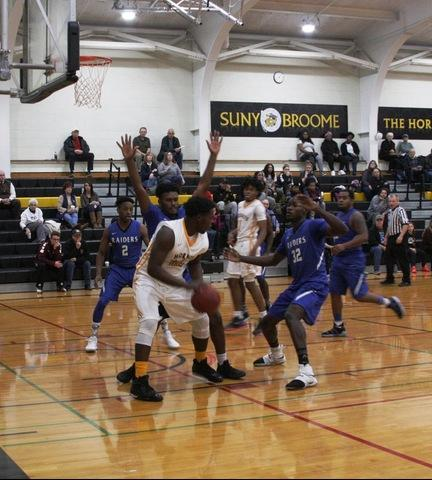 SUNY Broome men's basketball player surrounded by FM players under basket