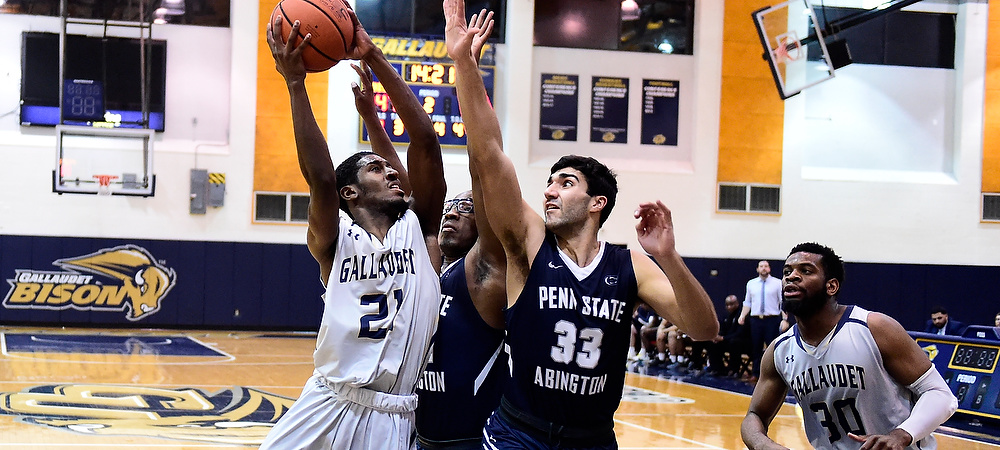 Gallaudet men's basketball player Corey Smith drives the baseline against two defenders. He tries to shoot an orange basketball above his head.