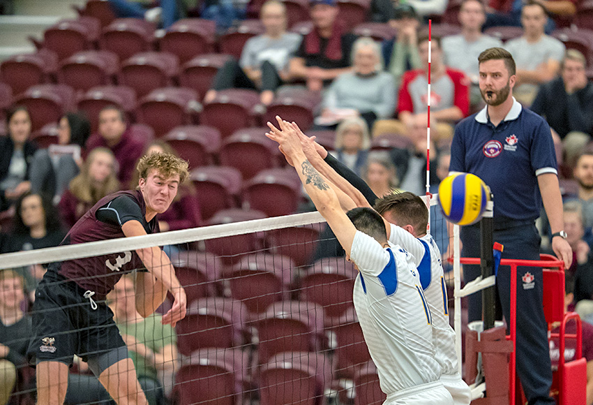 Jordan Peters hits one of his team-leading 13 kills through the UBC-Okanagan block on Friday night (Robert Antoniuk photo).