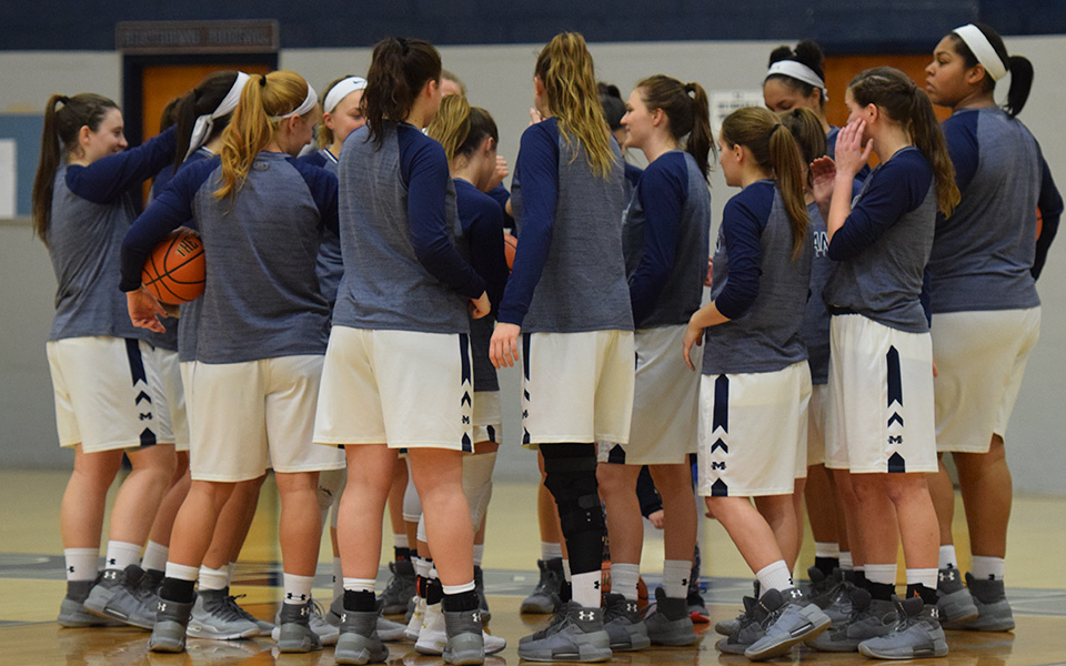 The Greyhounds huddle before a Landmark Conference game versus Goucher College in January 2018.