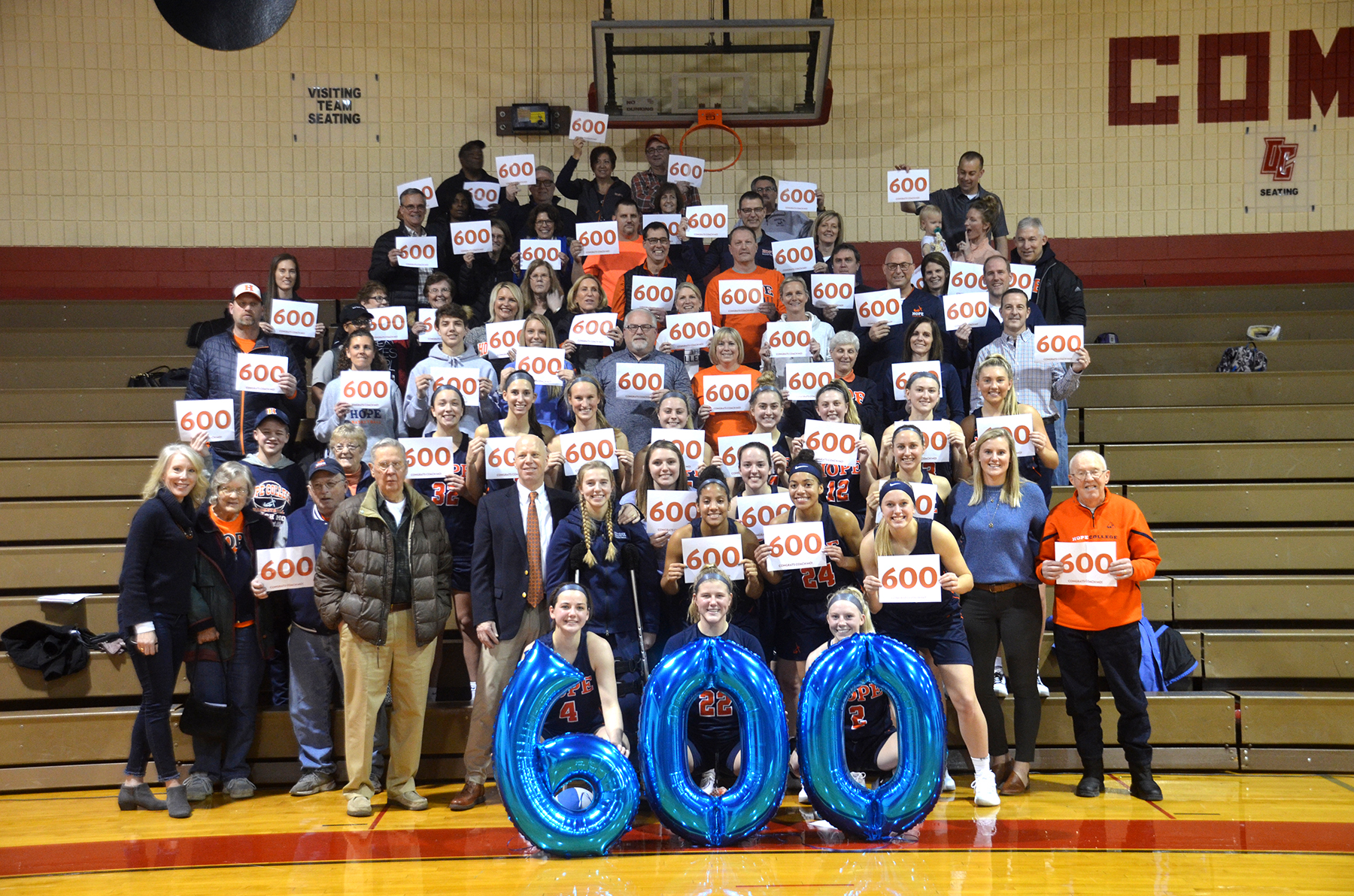 Head coach Brian Morehouse surrounded by his fans holding 600 signs after his 600th career victory