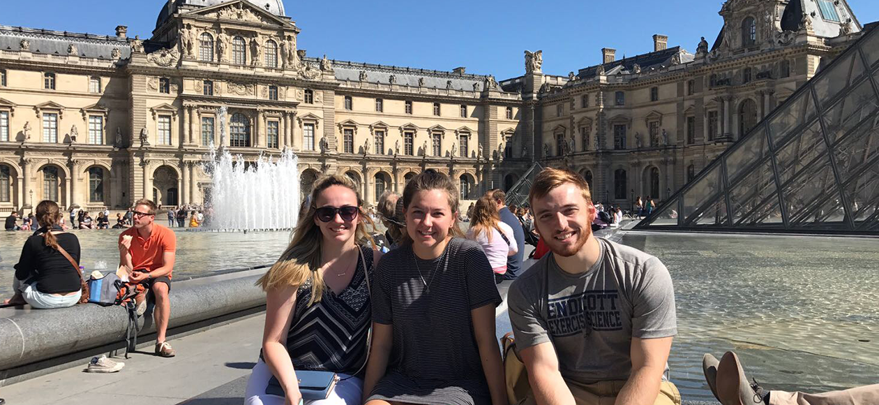 Holly Erbe takes a photo with friends in Europe.