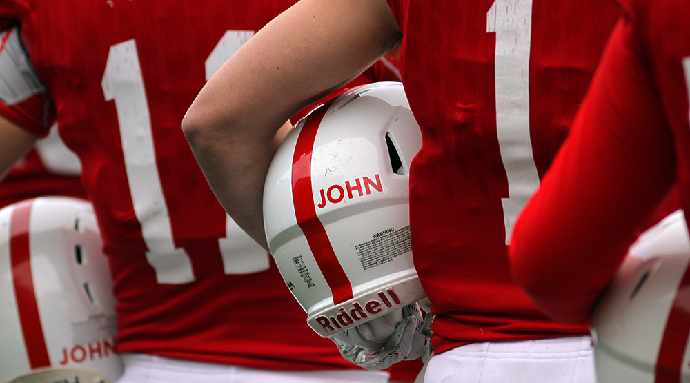 An unidentified St. John's player (shown from the back) stands with his helmet under his arm. The word JOHN is clearly visible, in red capital letters on a white helmet. (Photo by Wade Gardner, d3photography.com)