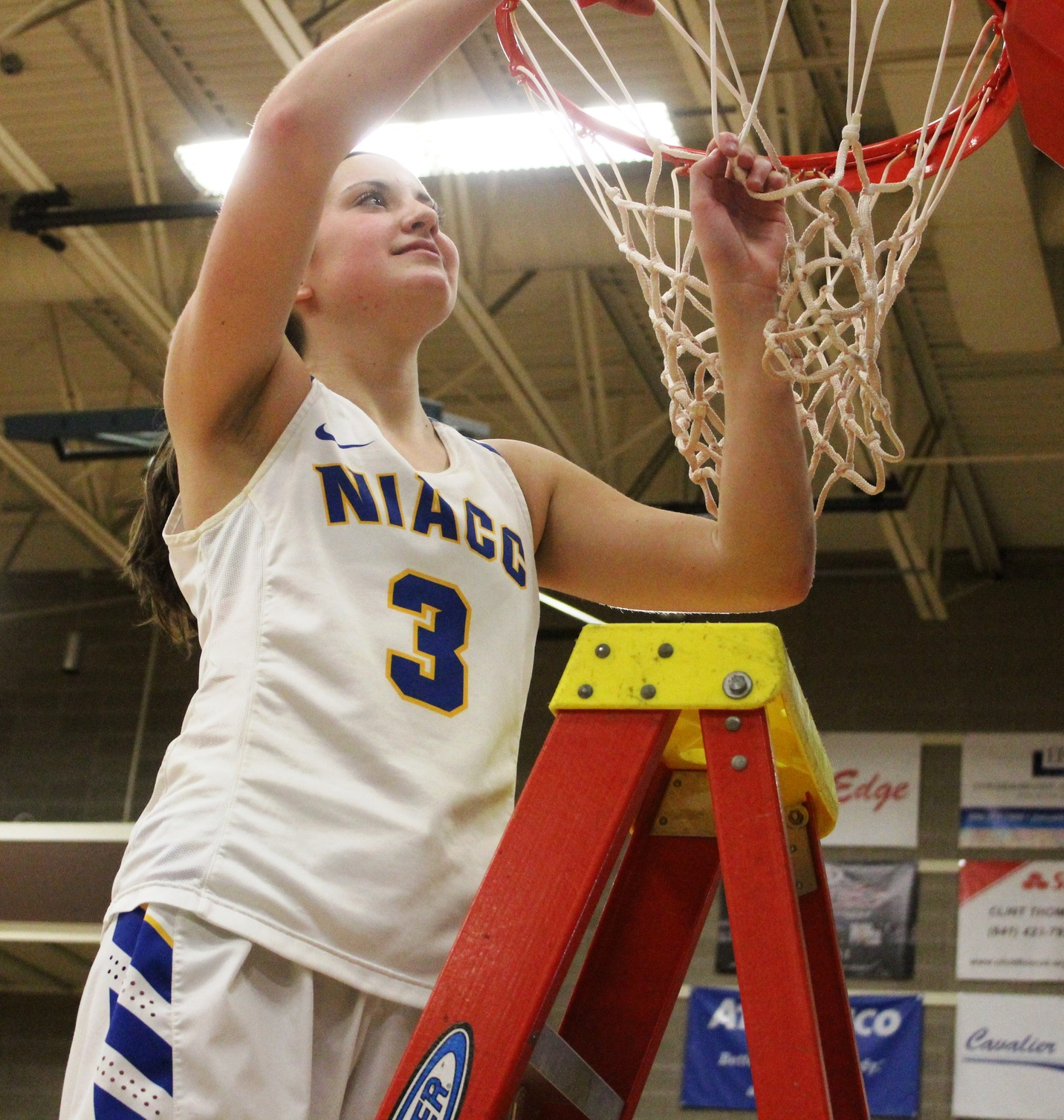 NIACC's Mandy Willems takes her turn cutting down the net after winning the regional title on Sunday in the NIACC gym.