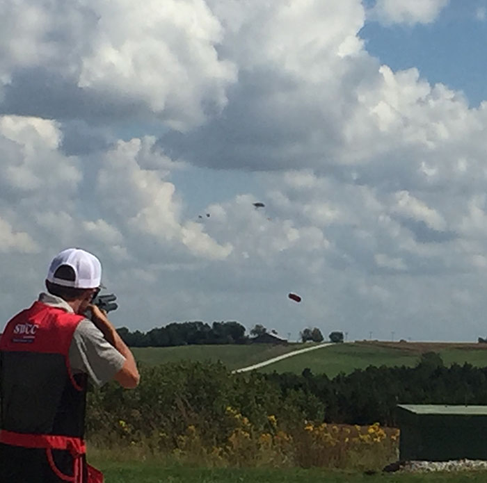 Spartan male sports shooter shoots at targets flying through the air.