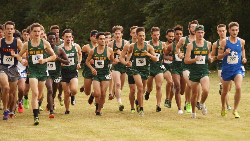 The men's cross country team runs out of the starting line in a pack.