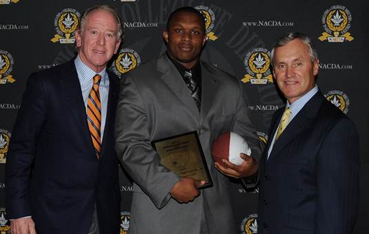 YSU defensive lineman Andrew Johnson poses with Archie Manning and Jim Tressel