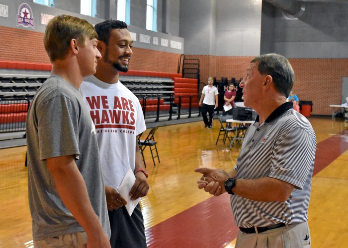 Huntingdon head coach Mike Turk welcomes back seniors Chip Taylor (left) and Anthony Wood (center) for the start of preseason camp. A total of 123 players reported for the Hawks on Tuesday.