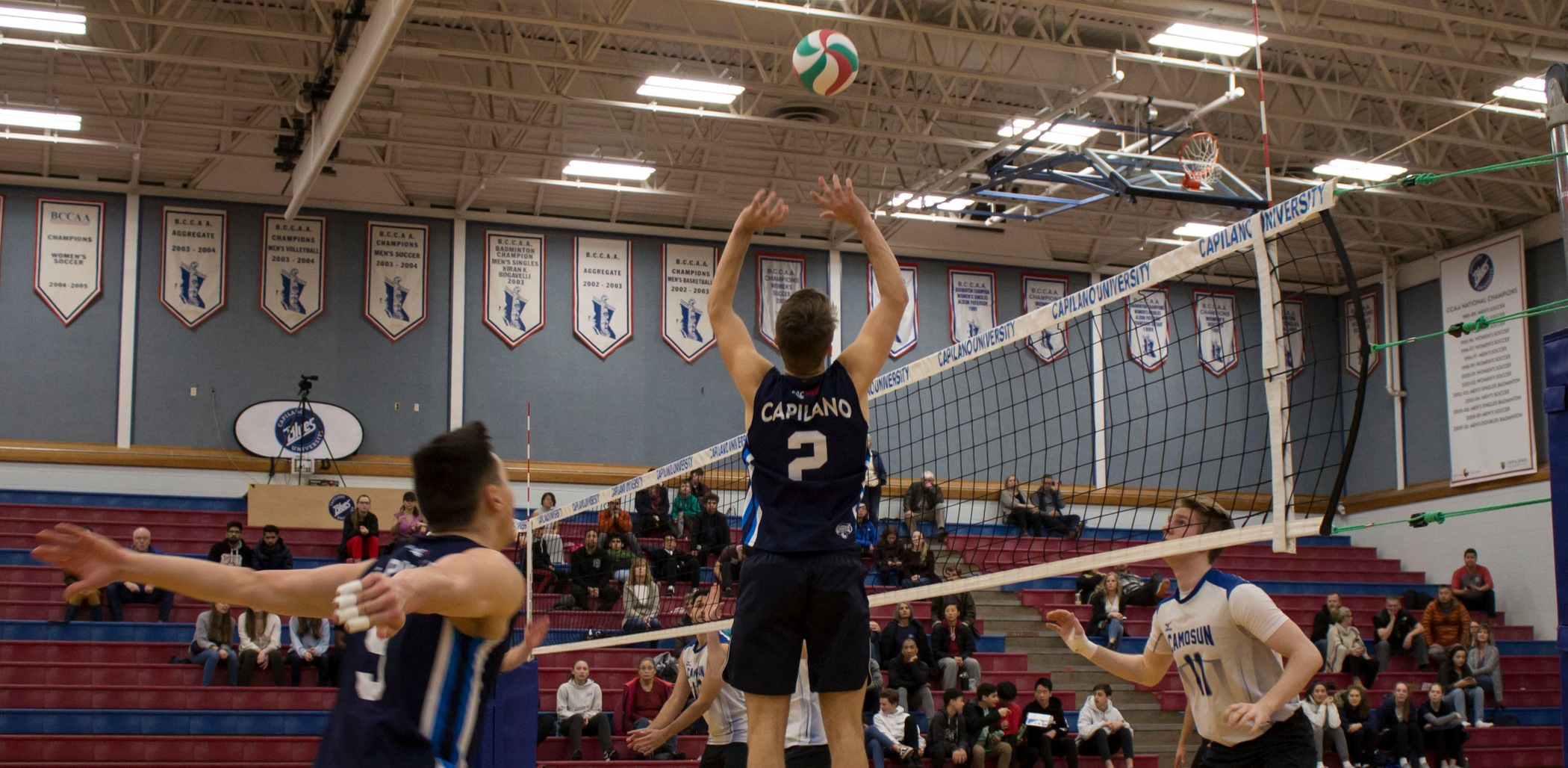 Setter Simon Friesen rises for a set, with outside hitter Justin Yee approaching for a hit. Photo CapU Athletics & Recreation