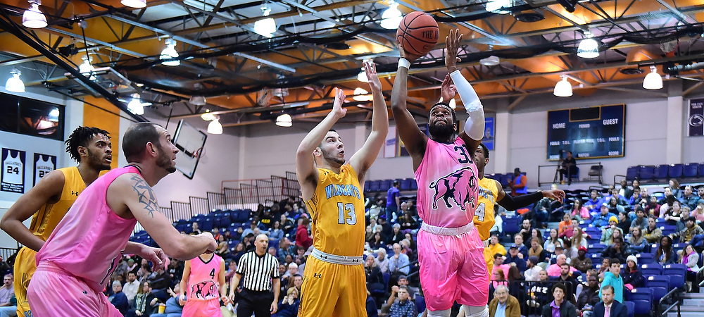 Gallaudet men's basketball player Jamal Garner drives the baseline against Cazenovia and shoots the ball towards the rim. The Bison are wearing special pink uniforms.