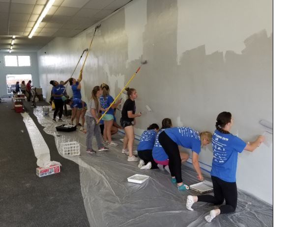 Photo of LCC team painting the walls of a hallway.