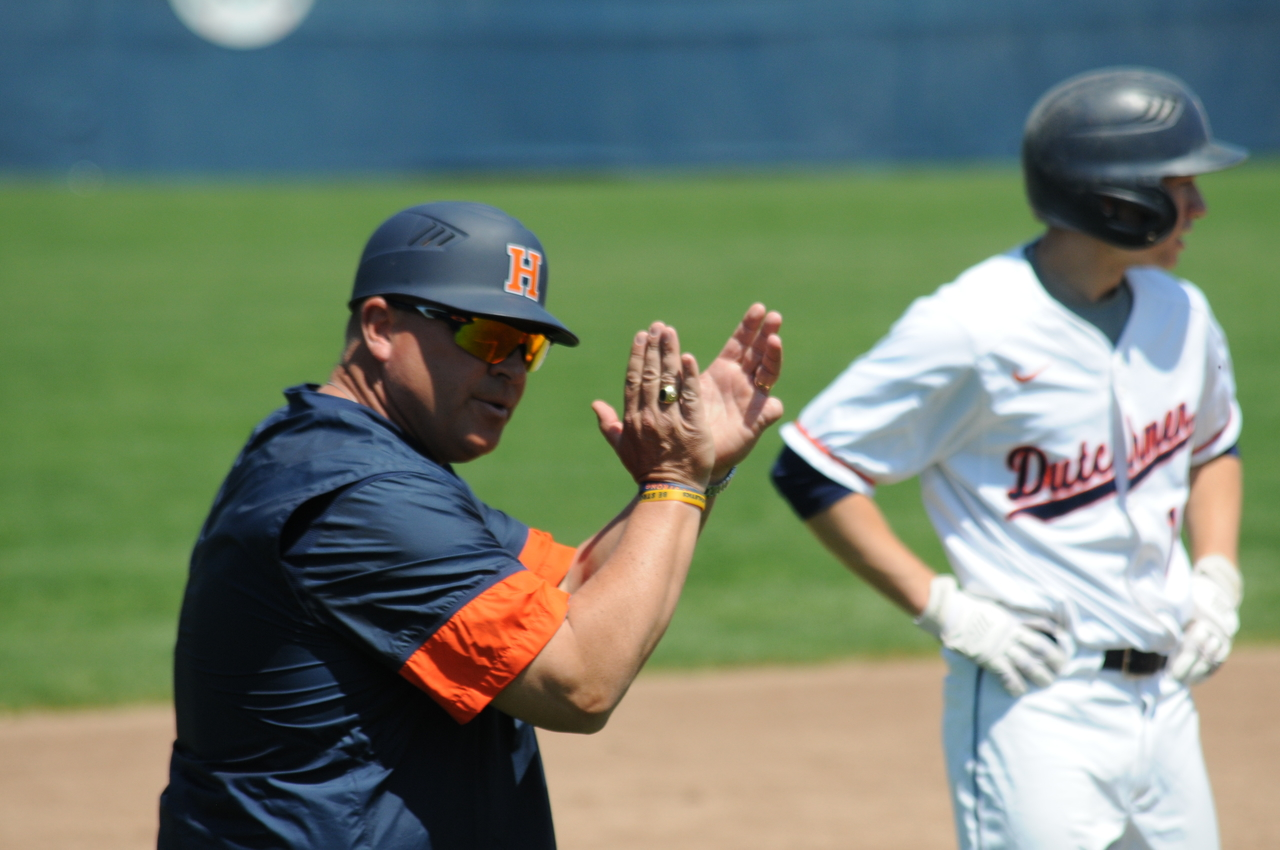 Head coach Stu Fritz clapping in the third-base coach's box