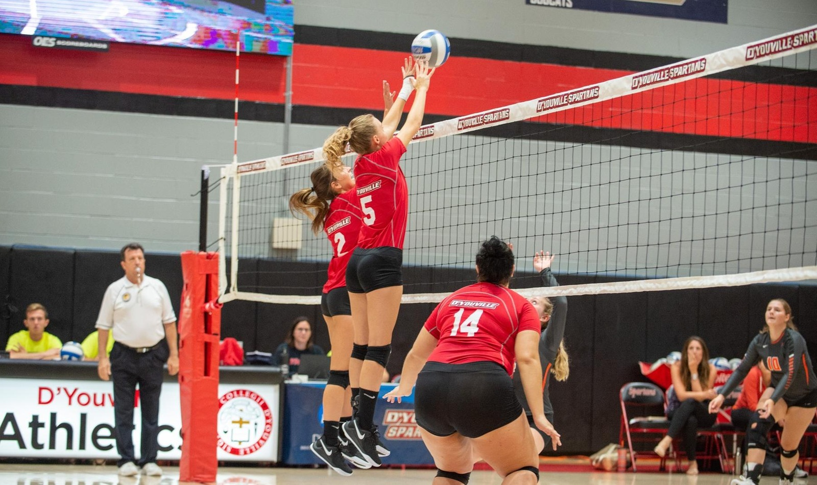 Talia Wright (2) and Carly Milleville (5) go up for a block at the net