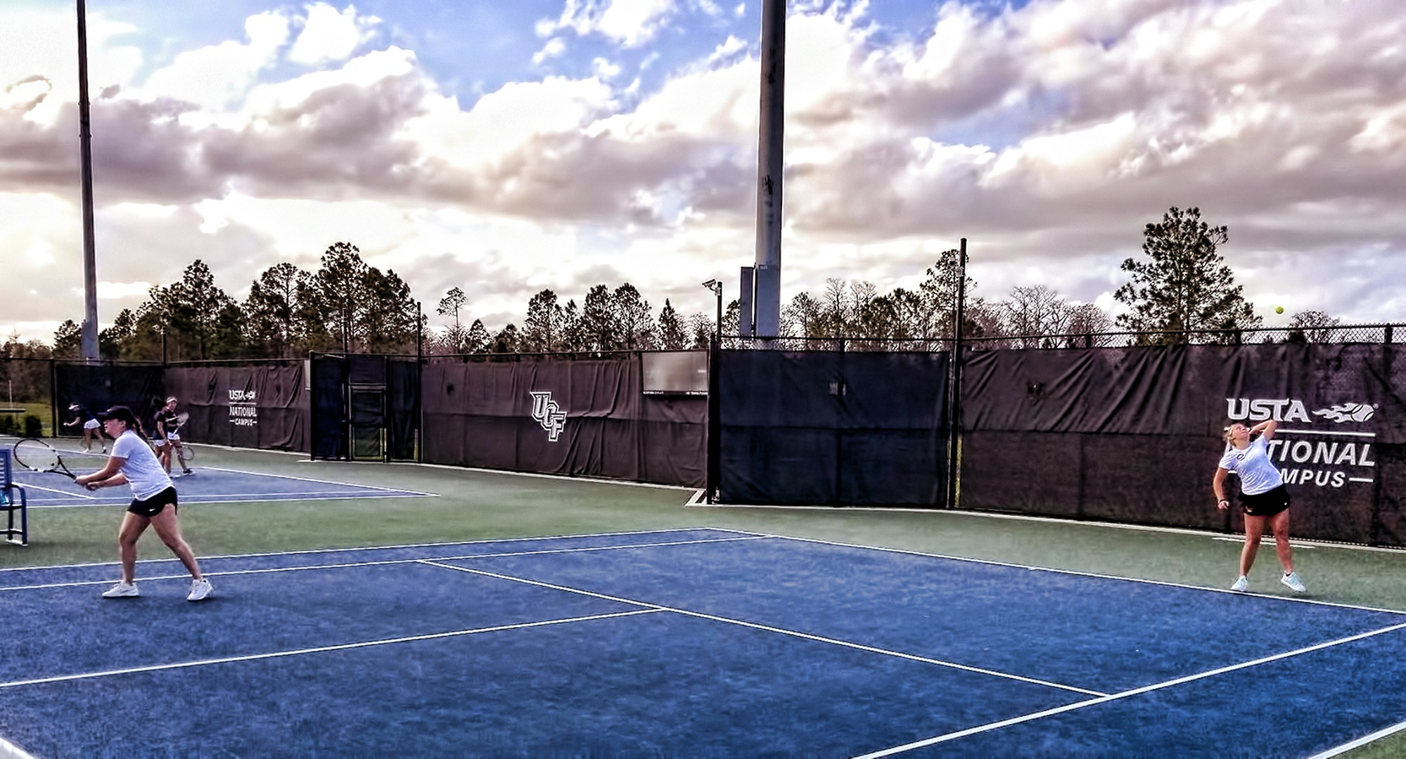 The doubles team of Lexi Johnson (R) and Josie Beachy serve during their match vs. Rose-Hulman. The duo were undefeated on the final day in Florida.