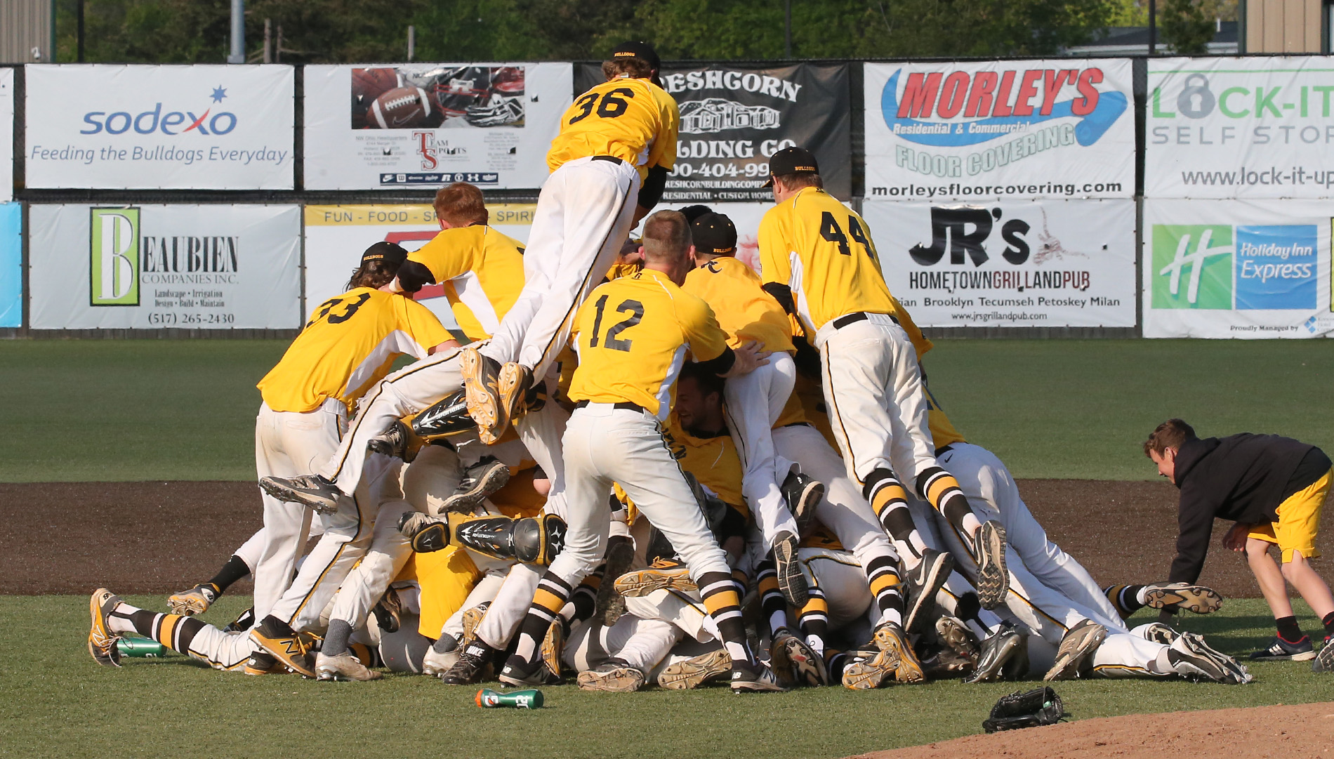 Players celebrate the 'Dogpile after the final out as the Adrian Bulldogs are the 2017 MIAA Baseball Tournament champions. (Action photo by Mike Dickie)