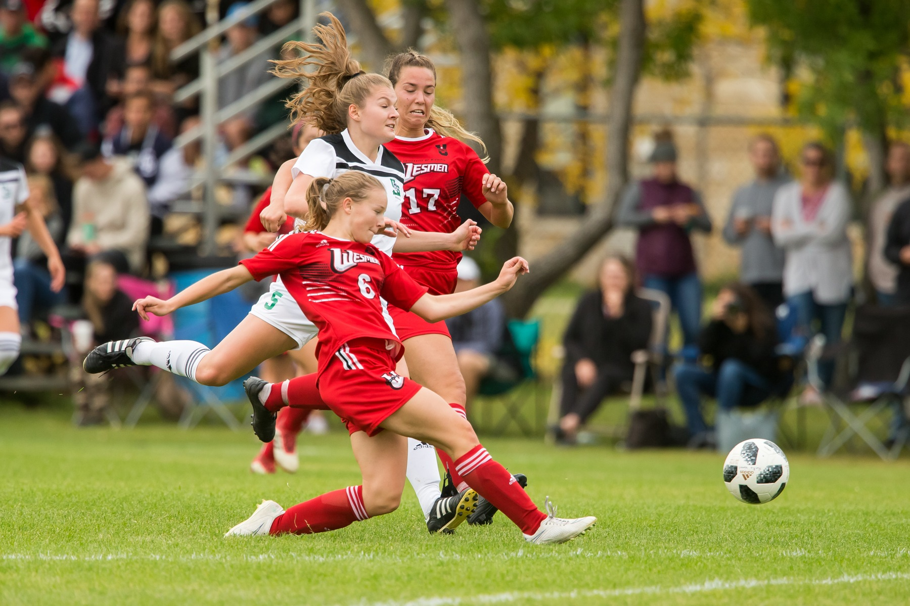 Wesmen defender Sara Boissonneault (6) slide tackles a Saskatchewan player during Canada West action Saturday in Saskatoon. (Huskie Athletics photo)
