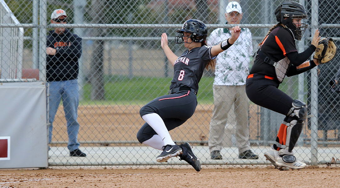 Samantha Whalen dives across home plate to score a run.