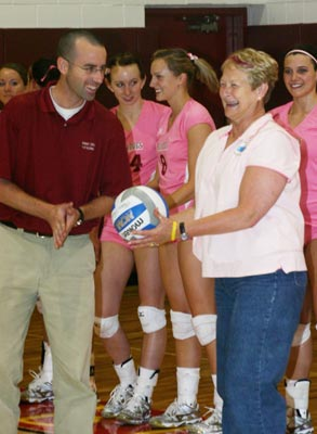 FSU Associate Athetics Director Jon Coles prrovides some serving tips to breast cancer survivor Terri Bloomquist. (Photo by Sandy Gholston)