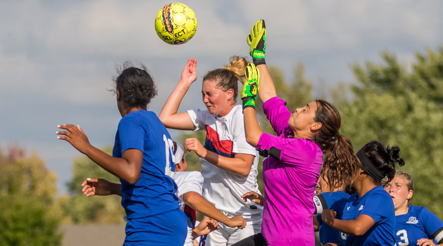 Ariel Wolff battles for a header against a pair of Pratt players in the first half of Friday's 4-0 victory by the No. 16 Blue Dragons over Pratt at the Salthawk Sports Complex. (Allie Schweizer/Blue Dragon Sports Information)