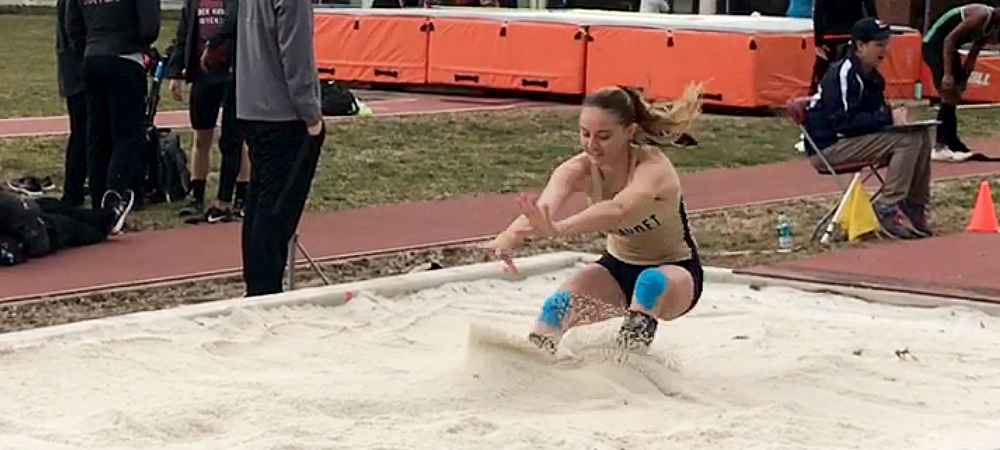 GU women's track and field jumper Hannah Wetzel jumps into a sand pit after her triple jump, jump.
