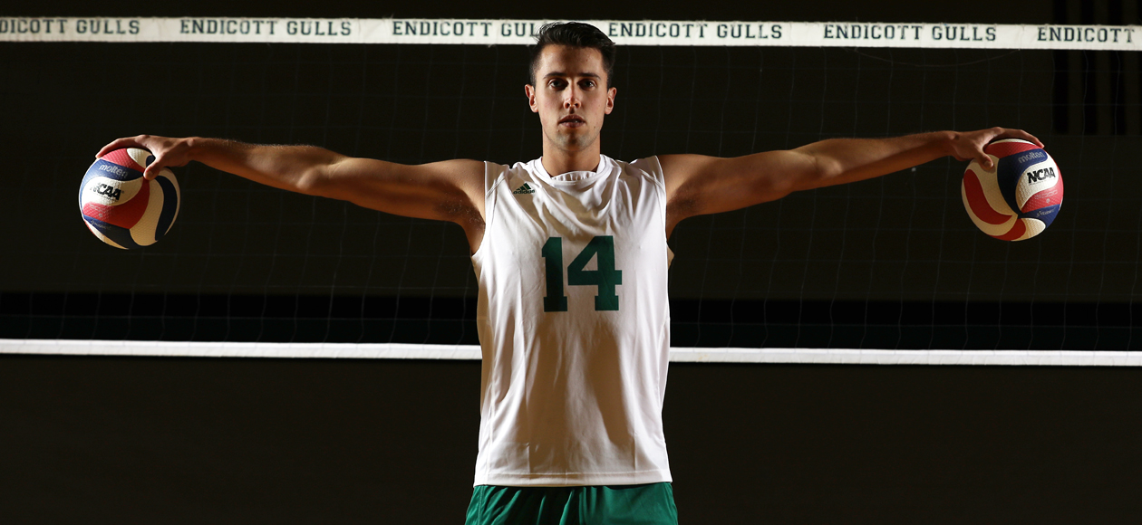 Posed photo of Jacob Newman holding two volleyballs.