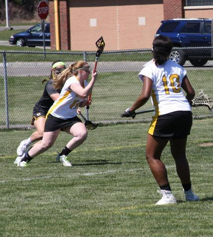 SUNY Broome women's lacrosse player running down field with ball