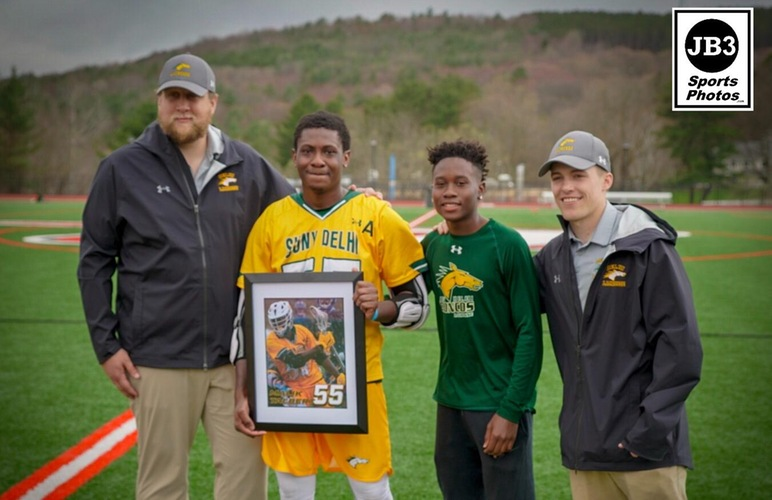 Malik Talbert alongside head coach Sam Miller, his brother, and assistant coach Zach Cook during his senior day recognition.