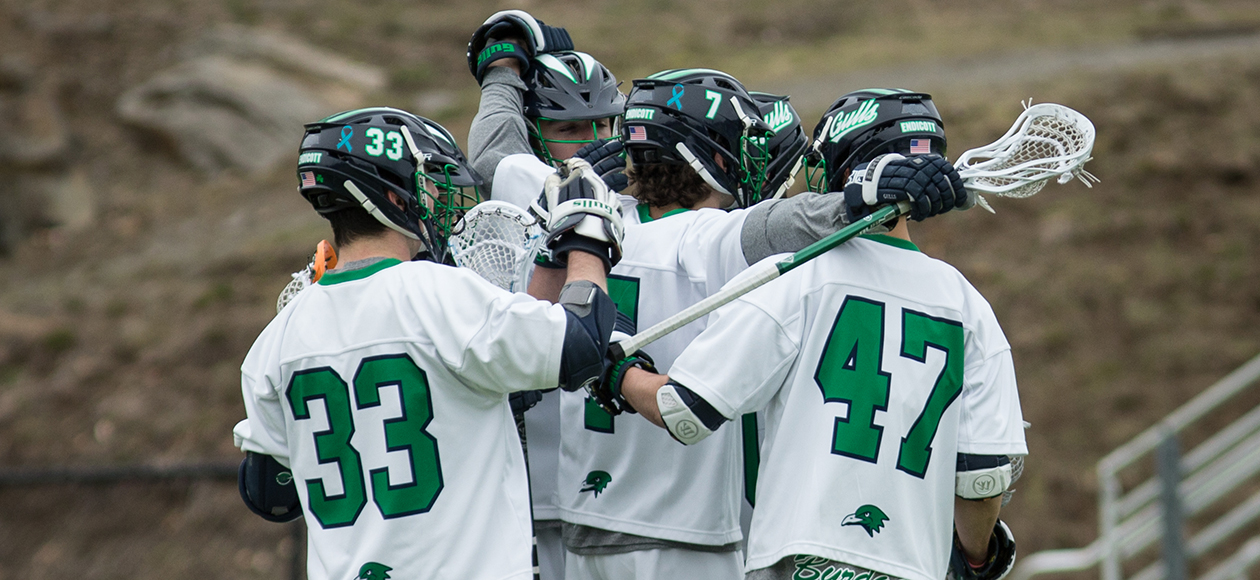 The men's lacrosse team huddles up after scoring a goal.