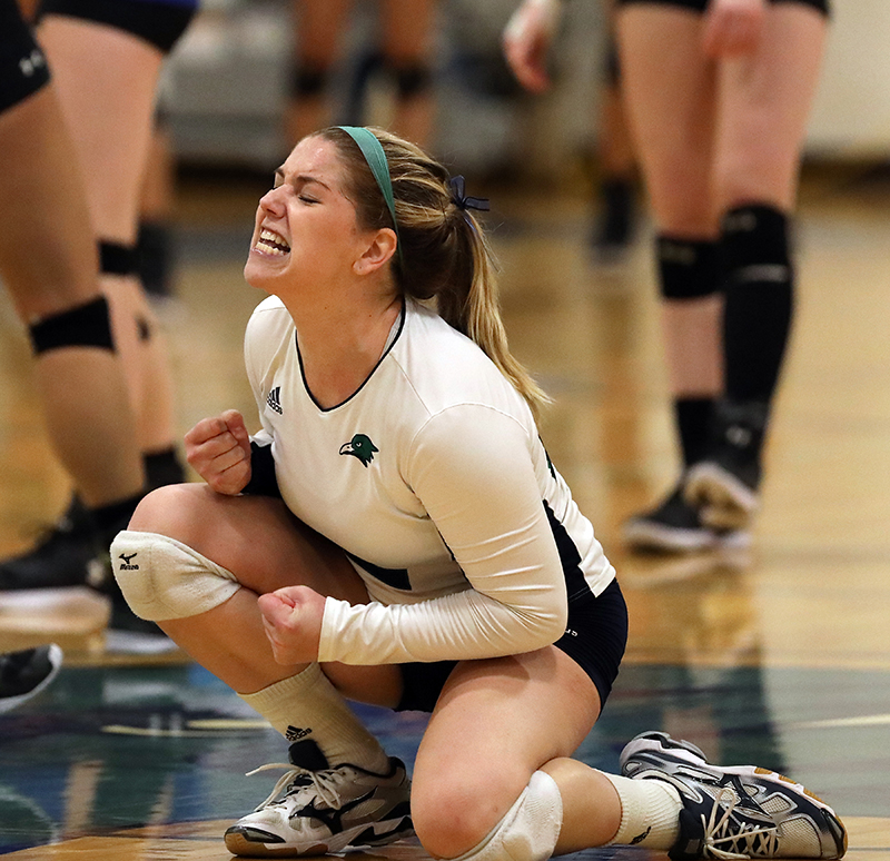 Lauren Sheehan celebrates a point by kneeling on the ground and pumping her fist.
