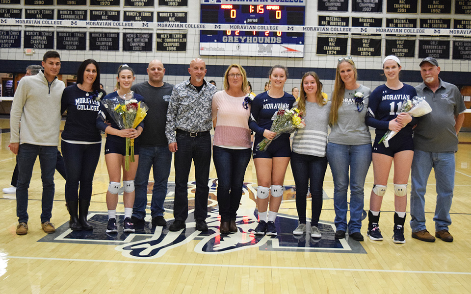 Seniors Brooke Kusmider, Rachel Farmer and Erin Tiger with their families on Senior Day in Johnston Hall versus Goucher College.